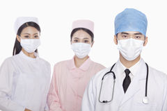 Portrait of serious healthcare workers with surgical masks, studio shot Stock Image