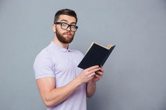Portrait of a serious hipster man holding book Royalty Free Stock Photography