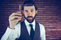 Portrait of serious hipster showing razor Royalty Free Stock Images