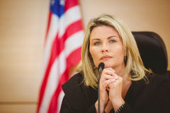 Portrait of a serious judge with american flag behind her Stock Photo