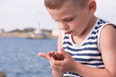 Portrait of a serious kid in singlet looking at his hands Royalty Free Stock Images