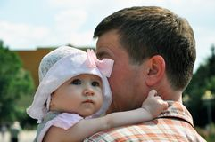 Baby girl in light hat embraces her father royalty free stock photography