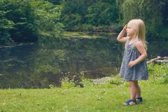 Portrait of serious little girl walking at river Stock Photography