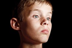 Portrait of a serious looking boy. Troubled and thoughtful young boy alone in the dark Stock Photography