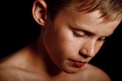 Portrait of a serious looking boy. Troubled and thoughtful young boy alone in the dark Royalty Free Stock Photos