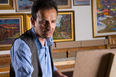Portrait of a serious male artist painting his masterpiece Royalty Free Stock Image