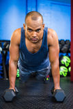 Portrait of serious male athlete doing push-ups with dumbbells Stock Images