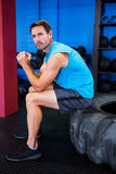 Portrait of serious male athlete sitting on tire Stock Photos