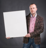 Portrait of a serious male holding blank white card. On a gray background royalty free stock images