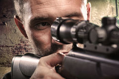 Portrait of serious man aiming with gun. In factory Stock Image