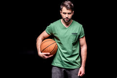 Portrait of serious man with basketball ball looking to camera. On black Stock Photography