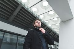 Portrait of a serious man with a beard and headphones on the neck against the backdrop of modern architecture. Royalty Free Stock Photography