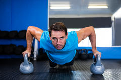Portrait of serious man doing push-ups with kettlebell Royalty Free Stock Photos