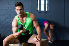 Portrait of serious man lifting dumbbell in gym royalty free stock photography