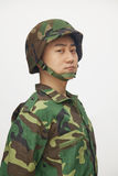 Portrait of serious man in military uniform and helmet, studio shot Stock Photography