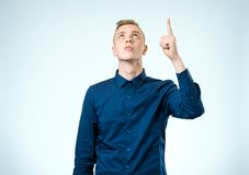 Portrait of a serious man pointing finger away isolated Stock Image