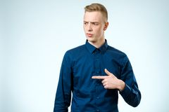 Portrait of a serious man pointing finger away isolated Royalty Free Stock Photography