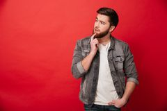 Portrait of serious man 30s in jeans jacket looking aside with b. Rooding gaze on copyspace isolated over red background Royalty Free Stock Photography