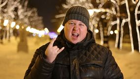 Portrait of serious man showing rock gesture outdoors during cold winter evening.  stock video footage