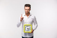 Portrait of a serious man showing wall clock royalty free stock images