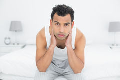 Portrait of a serious man sitting on bed Royalty Free Stock Photography