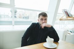 Portrait of a serious man in a suit who sits in a cafe with a cup of coffee and looks at the camera. Royalty Free Stock Images
