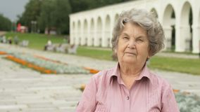 Portrait of serious elderly woman outdoors stock video