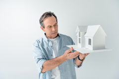 Portrait of serious mature man holding house model royalty free stock images
