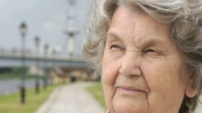 Portrait of serious mature old woman outdoors stock video