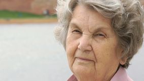 Portrait of serious mature old woman outdoors stock footage
