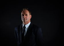 Portrait of a serious middle age businessman. On black backdrop with copyspace left and right Stock Photo
