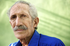 Portrait of serious old hispanic man looking at camera. Elderly people and emotions, portrait of serious senior caucasian man looking at camera against green Stock Photos
