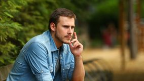 Pensive guy looking away in a park stock footage