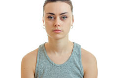 Portrait serious pretty girl in grey t-shirt that looks at camera isolated on a white background Royalty Free Stock Images