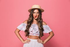 Portrait of serious pretty woman 20s wearing straw hat biting li. Ps and holding arms on waist isolated over pink background in studio royalty free stock photo