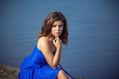 Portrait of serious and sad beautiful young brunette woman. Wearing elegant blue dress, sitting on a rock above the river Royalty Free Stock Photography