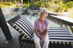 Portrait of serious senior woman sitting on lounge chair. At porch Royalty Free Stock Photos