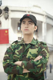 Portrait of Serious Solider With Arms Crossed, China, Chinese Flag in Background stock photo