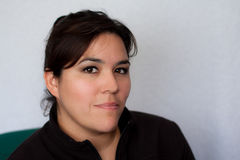 Portrait of serious or stern Hispanic woman. Portrait of dark haired and eyes Hispanic woman who has a serious expression or slightly stern expression.  Her hair Stock Images