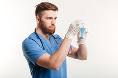 Portrait of a serious surgeon holding a syringe. Isolated on white background Stock Images