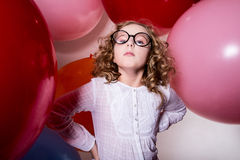 Portrait of serious teen girl on the background of large rubber. Balls. Important, capricious girl Royalty Free Stock Image