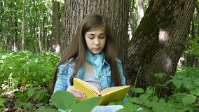 Portrait of serious teenage girl reading book and turning page leaning against tree trunk in forest in spring, studying stock video footage
