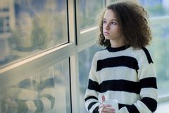 Serious teenage girl sitting by the window Royalty Free Stock Photos