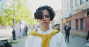 Portrait of serious teenager standing outside in the street on windy day. Looking at camera wearing white shirt and sweater. People and urban life concept stock video
