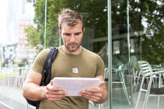 Portrait of serious urban man lwith tablet computer in the stree Royalty Free Stock Photo