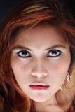 Portrait of a serious woman. Close up of a serious Asian female face with solemn stare Royalty Free Stock Photography