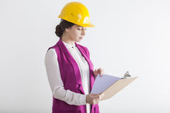 Portrait of a serious woman architect. Close up portrait of a serious woman architect wearing a pink vest and a yellow safety helmet and holding a clipboard Royalty Free Stock Images