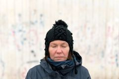 Portrait of serious woman with eyes closed on the street. On cold winter day stock photography