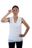 Portrait of serious woman with hand on hip adjusting invisible eyeglasses Royalty Free Stock Photos