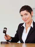Portrait of a serious woman knocking a gavel Royalty Free Stock Photography